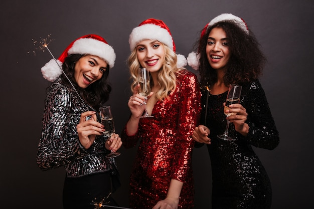 Afrikanische junge frau, die champagner in weihnachten trinkt