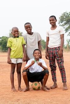 Afrikanische kinder mit fußball und medaille