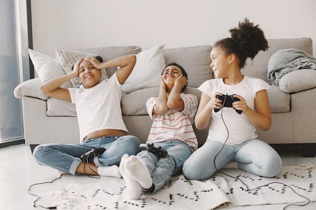 Afrikanische kinder spielen videospiele. kinder in leichter kleidung. controller in händen von kindern.