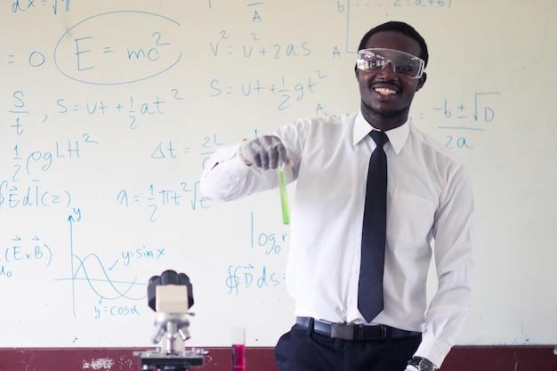 Afrikanische lehrer tragen eine brille, während sie mit naturwissenschaften experimentieren.