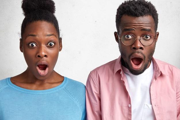 Afrikanische männliche und weibliche studenten sehen ungläubig mit offenem mund aus, informieren sich über die morgige prüfung und haben schockierte gesichtsausdrücke