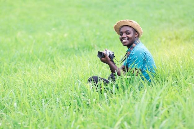 Afrikanische mannreisende fotografieren und lächeln glücklich zwischen grünen wiesen.