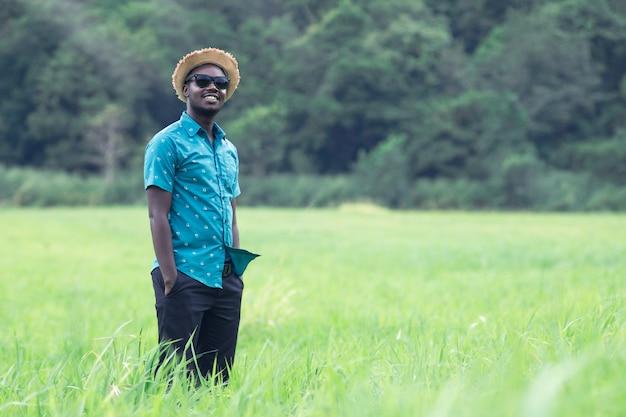Afrikanische mannreisende stehen und lächeln glücklich zwischen grünen wiesen.