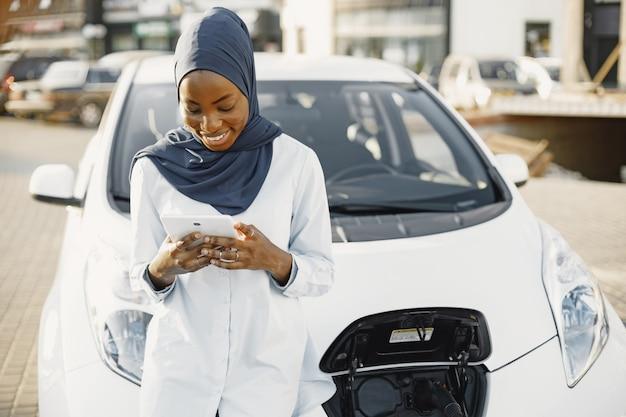 Afrikanische muslimische frau, die sich auf ihr auto stützt und eine digitale tablette hält. remote arbeiten oder informationen teilen.