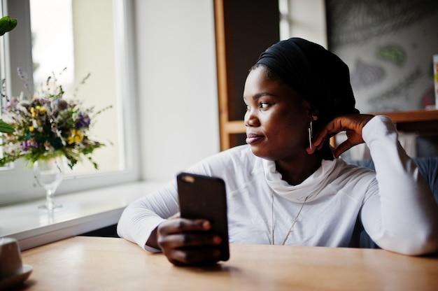 Afrikanische muslimische frau im schwarzen hijab, der im café mit handy zur hand sitzt