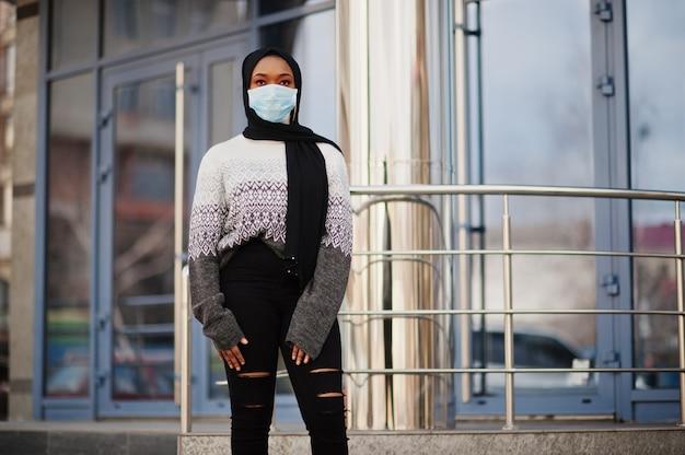 Afrikanische muslimische junge freiwillige frau, die gesichtsmaske und schwarzen hijab im freien trägt. coronavirus-quarantäne und globale pandemie.