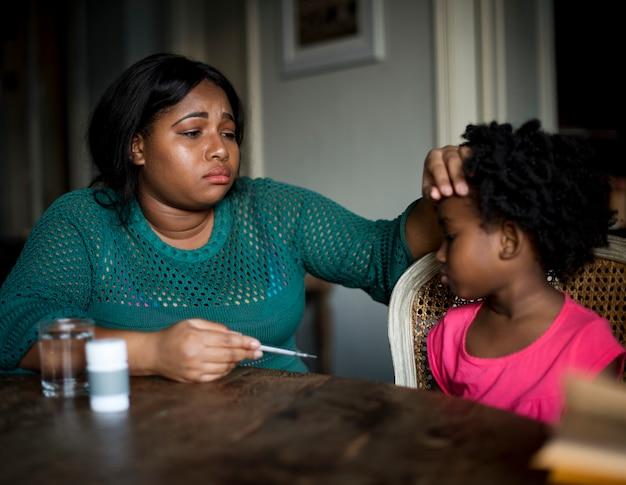 Afrikanische mutter, die um ihrer kranken tochter sich kümmert