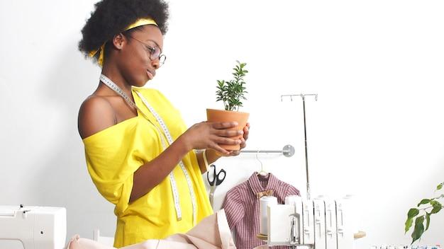 Afrikanische näherin, modedesignerin, die mit stoff arbeitet, arbeitsplatz der näherin in der werkstatt. die afroamerikanische frau arbeitet in ihrer werkstatt an selbstisolation.