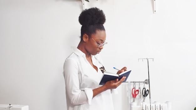Afrikanische näherin, modedesignerin, die mit stoff arbeitet, arbeitsplatz der näherin in der werkstatt