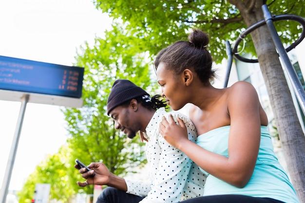 Afrikanische paare, die am busbahnhof warten