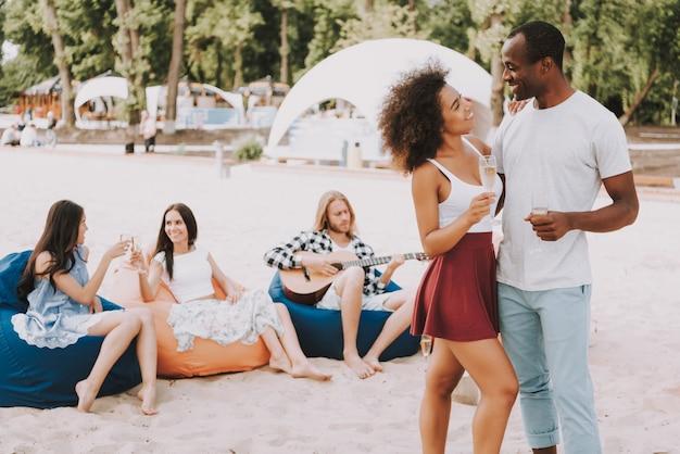 Afrikanische paare haben champagne dancing auf strand