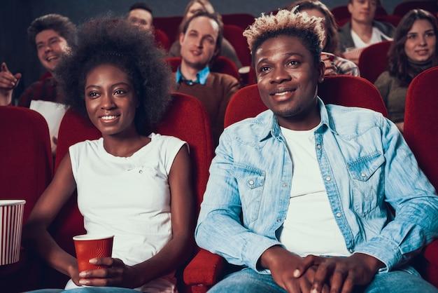 Afrikanische paare mit aufpassendem film des popcorns im kino