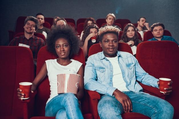 Afrikanische paare mit aufpassendem film des popcorns im kino.