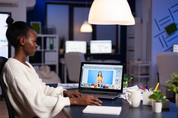 Afrikanische professionelle fotoretuschefrau, die nachts an einem neuen projekt im geschäftsbüro am laptop arbeitet