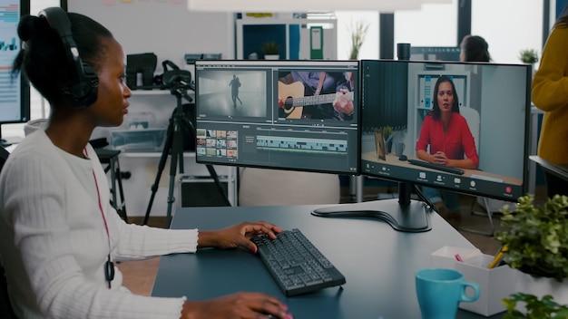 Afrikanische redakteurin mit headset, die während der online-konferenz spricht