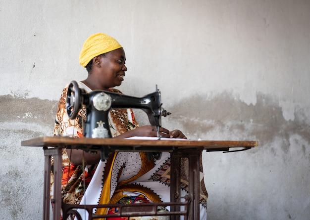Afrikanische schneiderin arbeitet an nähmaschine