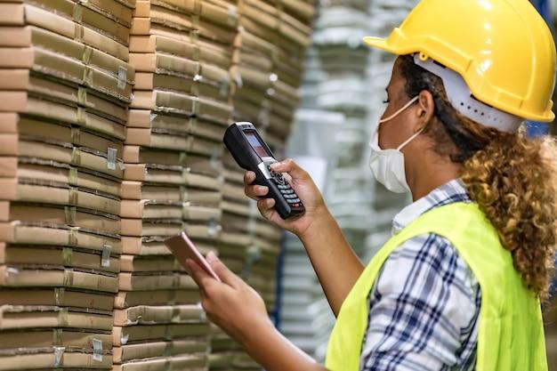 Afrikanische schwarze lagerarbeiterin mit gesichtsmaske, die waren prüft, verwendet digitales tablett und barcode-scanner, sie trägt gesichtsmaske, die von covid-19 nach wiedereröffnung der fabrik verhindert.