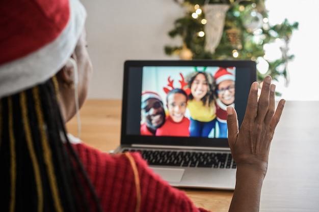 Afrikanische seniorin, die während der weihnachtszeit videoanrufe mit ihrer familie macht - fokus auf der rechten hand