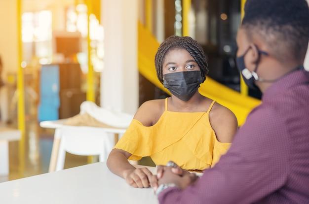 Afrikanische studenten mit freunden, die eine maske tragen, die an der modernen schule am schreibtisch sitzt. virenschutz in der schule. selektiver fokus