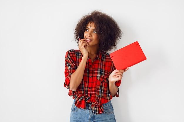 Afrikanische studentin mit buch, das innen über weißer wand aufwirft. tragen eines rot karierten hemdes. blaue jeans.