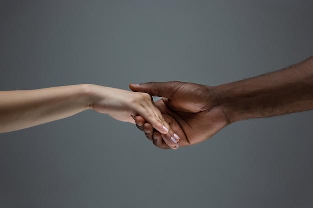 Afrikanische und kaukasische hände gestikulieren