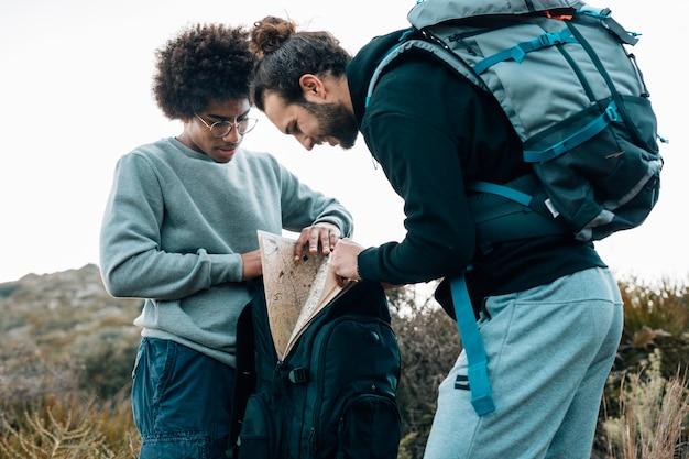 Afrikanische und kaukasische junge männer, die nach karte im rucksack suchen