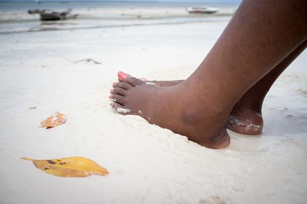 Afrikanische weibliche füße auf strandsand