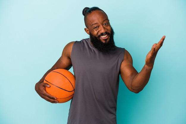 Afrikanischer amerikanischer mann, der basketball einzeln auf blauem hintergrund spielt, der eine angenehme überraschung erhält, aufgeregt und die hände hebt.