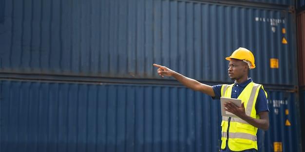 Afrikanischer arbeiter, der eine tablette hält, die containerbox vom frachtschiff für den export und import überprüft