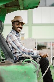 Afrikanischer arbeiter, der schwere baumaschinen baggerlader mit lächeln und glücklich fährt