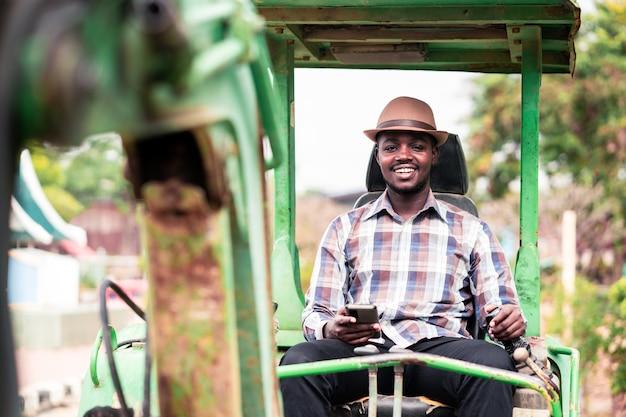 Afrikanischer arbeiter, der schwere baumaschinen baggerlader mit smartphone fährt