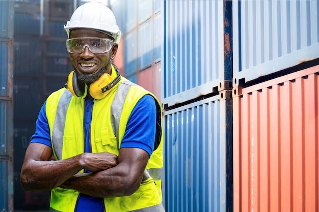 Afrikanischer arbeiter des fabrikingenieurs, der vertrauen mit grünem arbeitsanzugkleid steht
