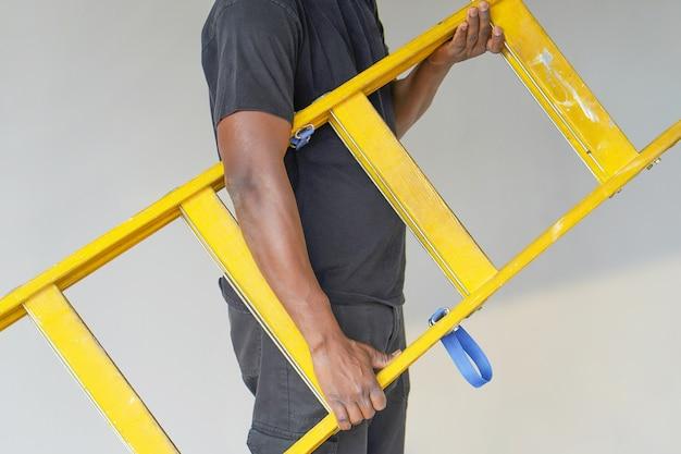 Afrikanischer arbeiter mit holzleiter