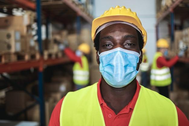 Afrikanischer arbeitermann innerhalb des lagers, während sicherheitsmaske verwendet - fokus auf gesicht