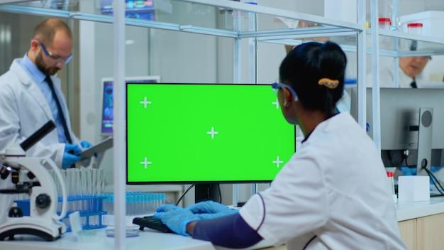 Afrikanischer arzt, der im modern ausgestatteten labor am computer mit grünem bildschirm arbeitet. multiethnisches team von mikrobiologen, die impfstoffforschung betreiben und auf einem gerät mit chroma-key schreiben, isoliert, mockup-display.