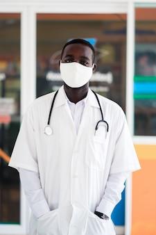 Afrikanischer arzt trägt gesichtsmaske und hält stethoskop