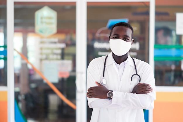Afrikanischer arzt tragen gesichtsmaske mit stethoskop