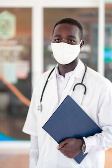Afrikanischer arzt tragen gesichtsmaske und stethoskop mit professionell und freundlich