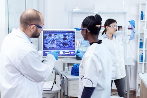 Afrikanischer arzt und wissenschaftler, die virenexperimente mit computersoftware durchführen. multiethnisches team medizinischer forscher, die im sterilen labor mit schutzbrille und handschuhen zusammenarbeiten.
