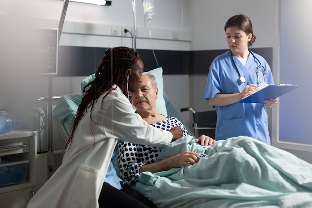 Afrikanischer arztspezialist, der mit stethoskop hört, das herz des älteren mannes im bett liegt und mit ...