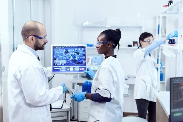 Afrikanischer assistent, der mit wissenschaftlern über virusexperimente im chemielabor diskutiert. multiethnisches team medizinischer forscher, die im sterilen labor mit schutzbrille und handschuhen zusammenarbeiten