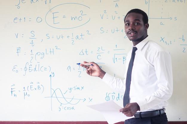 Afrikanischer ausländischer lehrer, der wissenschaft im klassenzimmer unterrichtet.