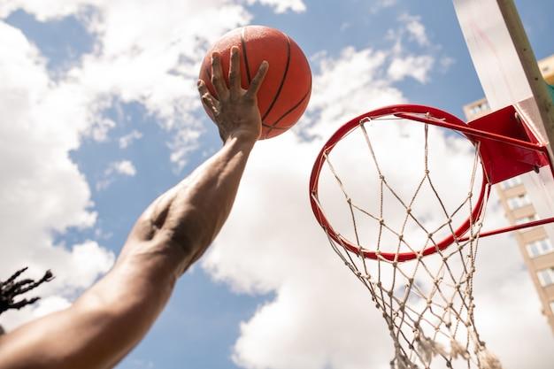 Afrikanischer basketballspieler, der ball während des spiels oder des trainings mit bewölktem himmel oben in korb wirft