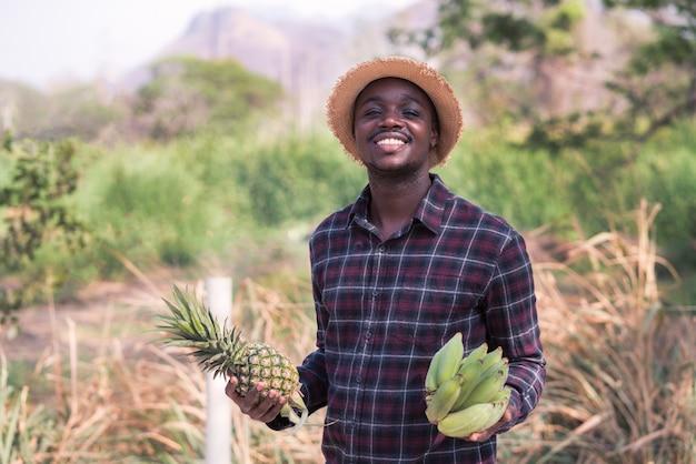 Afrikanischer bauernmann, der ananas und banane am bio-bauernhof mit lächeln und glücklich hält. landwirtschafts- oder kultivierungskonzept