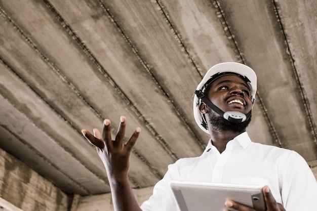 Afrikanischer bauingenieur, der tablette beim tragen des sturzhelms spricht und hält.