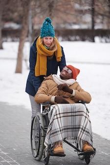 Afrikanischer behinderter mann im rollstuhl, der mit seinem assistenten im freien geht