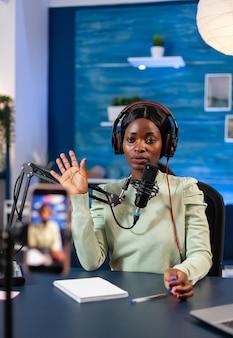 Afrikanischer blogger, der in die kamera schaut und zur kamera-aufnahme-episode für eine online-show winkt. sprechen während des livestreamings, blogger diskutieren im podcast mit kopfhörern.