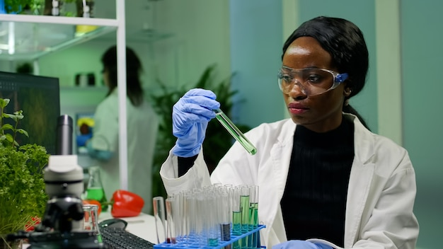 Afrikanischer botaniker, der reagenzgläser mit dna-testflüssigkeit überprüft, die biologieprobe für botanikexperiment untersucht. wissenschaftlerin, die im landwirtschaftslabor arbeitet, das eine öko-umgebung entwickelt