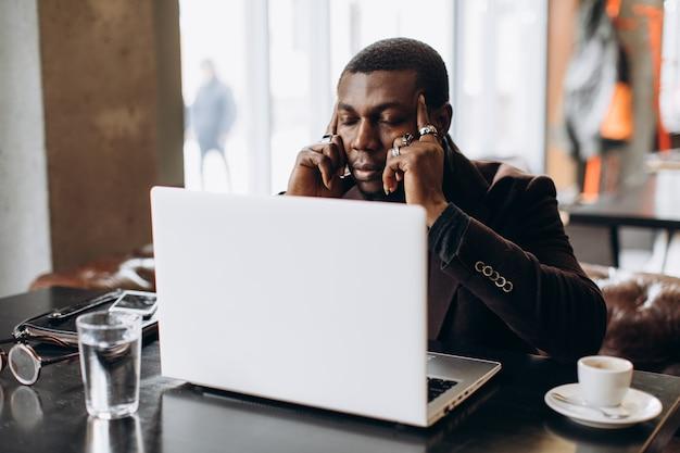 Afrikanischer denkender geschäftsmann und beim arbeiten an laptop in einem restaurant müde.