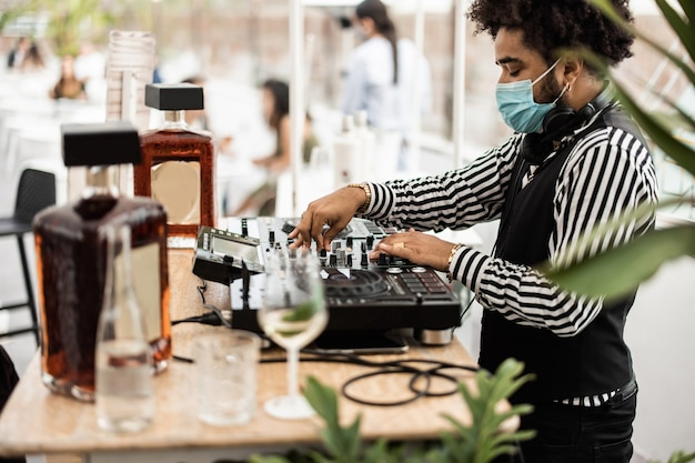 Afrikanischer dj, der musik in der cocktailbar im freien spielt, während er eine gesichtsschutzmaske trägt - hauptfokus auf der oberen hand